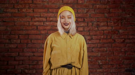 mordendo : Young curly woman in total trendy yellow look. Portrait of flirting beautiful girl on orange bricks wall studio background. Stock Footage