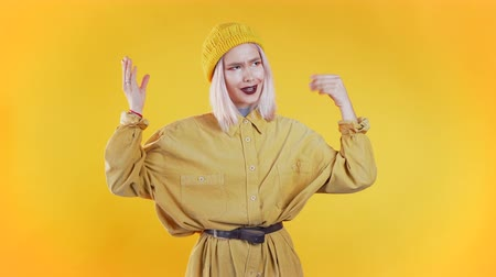 compositing : Pretty millenial girl showing with hands and two fingers like quotes gesture, bend fingers isolated over yellow background. Very funny, irony and sarcasm concept.