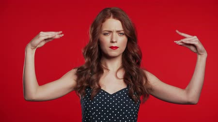 compositing : Pretty millennial girl showing with hands and two fingers like quotes gesture, bend fingers isolated over red background. Very funny, irony and sarcasm concept.