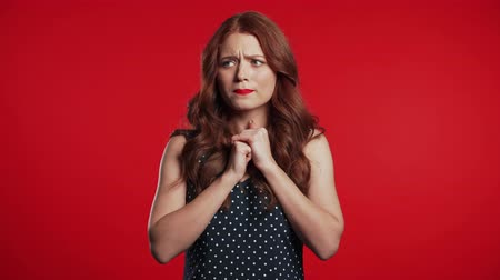 Young frightened girl shocked isolated over red background. Stressed and depressed woman because of bad news