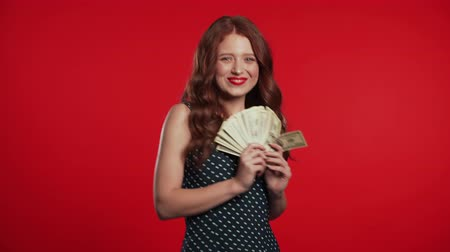 Satisfied happy excited girl showing money - U.S. currency dollars banknotes on red wall. Symbol of success, gain, victory.