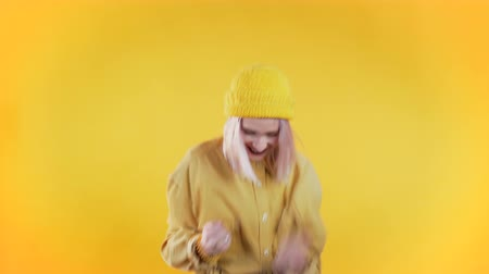 Punk girl with pink hair very glad and happy, she shows yes gesture of victory, she achieved result, goals. Surprised excited happy woman on yellow background Wideo
