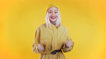 Girl with pink hair very glad and happy, she shows yes gesture of victory, she achieved result, goals. Surprised excited happy woman on yellow background