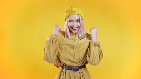 Portrait of girl with pink hair, she shows wow delight effect gesture. Surprised excited happy woman. Pretty female shocked model on yellow background. Wideo