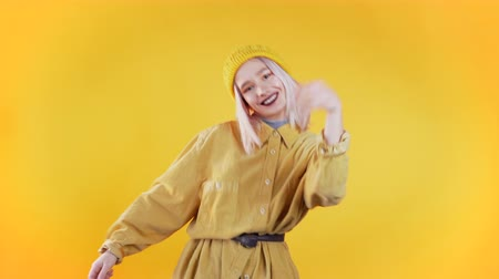 Beautiful woman with pink hair and piercing dancing and snaps fingers on colorful yellow studio background. Cute girls portrait. Party, happiness, freedom, youth concept.