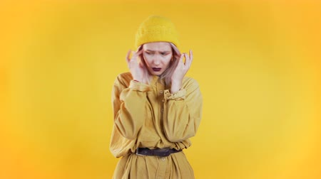Young upset woman with curly hair having headache, studio portrait. Girl putting hands on head, isolated on yellow background. Concept of problems and headache.