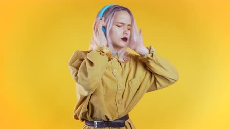 Beautiful woman with pink hair dancing with headphones on yellow studio background. Cute girls portrait. Music, radio, happiness, freedom, youth concept.