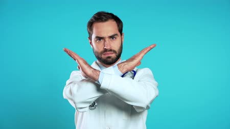 sebész : Portrait of serious doctor in professional medical white coat with no crossing hands sign make negation gesture. Denying, Rejecting, Disagree. Doc man isolated on blue background.