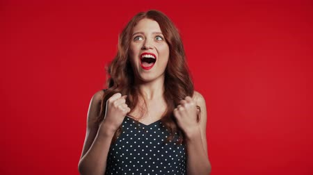 удивительный : Portrait of girl with red hair, she shows YES gesture. Surprised excited happy woman. Pretty female shocked model on studio background.