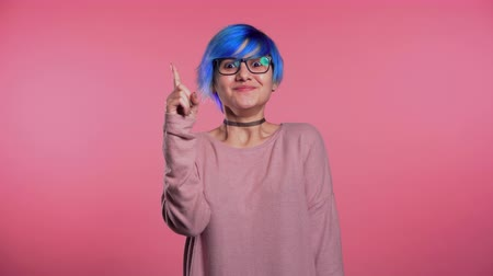 arcszín : Portrait of young thinking pondering woman with unusual blue hairstyle having idea moment pointing finger up on pink studio background. Smiling happy girl showing eureka gesture.