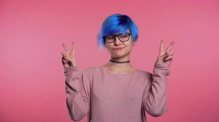 irony : Pretty punk girl with blue hair showing with hands and two fingers like quotes gesture, bend fingers isolated over pink background. Very funny, irony and sarcasm concept.