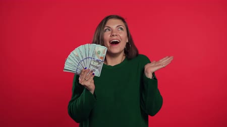 賃金 : Happy excited girl in green sweater showing money - U.S. currency dollars banknotes on red wall. Symbol of success, gain, victory. 動画素材