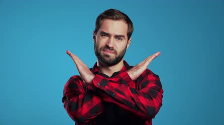 запретить : Young man with beard making no crossing hands sign, negation gesture over blue studio background