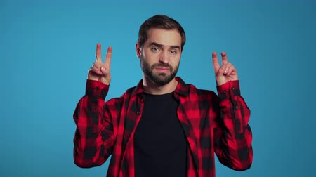 irony : Man with beard showing with hands and two fingers like quotes gesture, bend fingers isolated over blue background. Very funny, irony and sarcasm concept.