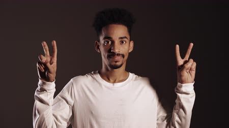 irony : African american man showing with hands and two fingers like quotes gesture, bend fingers isolated over dark background. Very funny, irony and sarcasm concept. Stock Footage