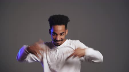çok güzel : Young very active and energetic african american man in white wear smiling and dancing in good mood on grey background. 4k