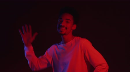 çok güzel : Young very active and energetic african american man in white wear smiling and dancing in good mood on dark background with red neon light. 4k