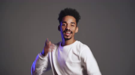 çok güzel : Young very active and energetic african american man in white wear smiling and dancing in good mood on grey background. Stok Video