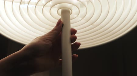 kompakt : Close up shot of female hand turn on table lamp. Early morning, get up concept. White color. Unrecognizable woman, slow motion. Stok Video