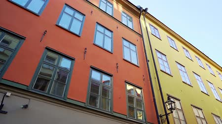 Apartment buildings on european streets in old northern city. Scandinavian windows. Facades of colorful houses in narrow streets of Stockholm, Sweden. Traveling concept. Slow motion.