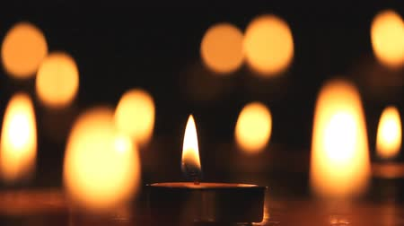 religioso : Candles light, black background.