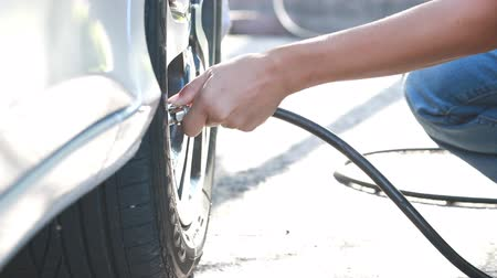 pneus : close up,woman checking pressure and inflating car tire.
