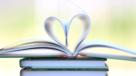 поток : Book stack open page heart shape in wind, green garden background Стоковые видеозаписи