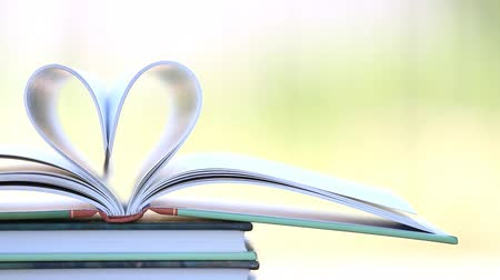 öykü : Book stack open page heart shape in wind, green garden background Stok Video