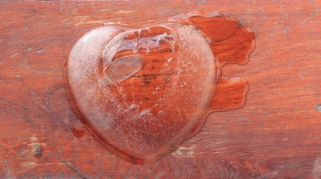 heart shaped : Ice heart shape melt on wood background.time lapse clip.