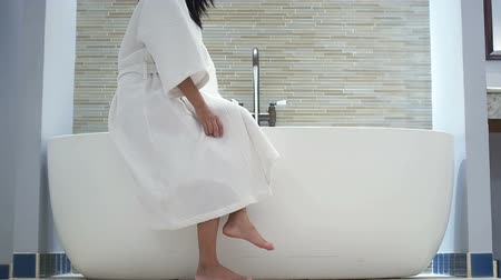 hot tub : Asian woman turning tap and pouring water into bathtub and undress bathrobe . Stock Footage