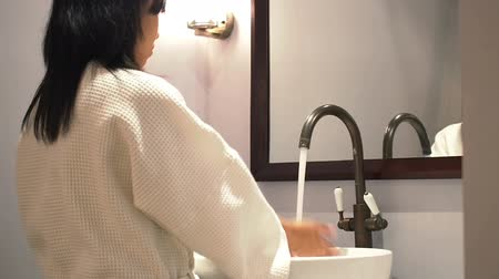 mycie rąk : Asian woman washing hand on basin bathroom and Look at mirror. Wideo