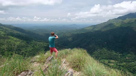 шри : Adventure photographer with camera shoots while standing in mini Adams peak in Sri Lanka. Great view from the top. Concept of making photos for good memories