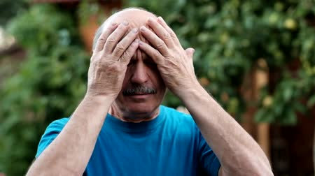 bolest hlavy : Caucasian man showing how much his head hurts, looking miserable and exhausted standing outdoor in garden. Health problem with migraine Dostupné videozáznamy