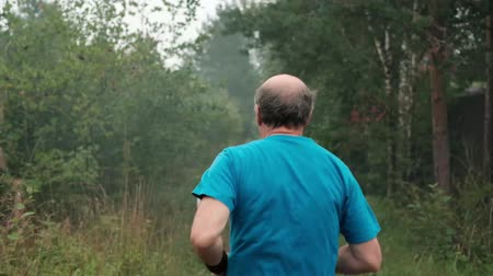 kolsuz : Mature man running on road through trees. Back view. Senior male having active lifetyle during summer vacation in Russia Stok Video