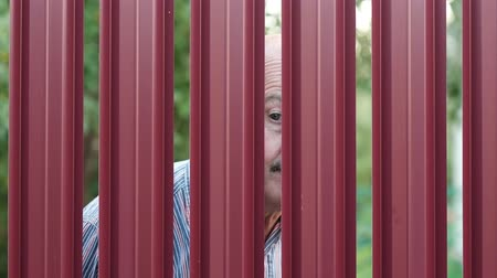 sąsiadka : Senior man looking through fence spying on his neighbor. Curious pensioner want to see what is going on outdoor