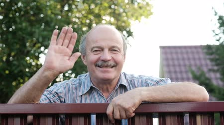 do widzenia : Friendly caucasian old man waving hi or farewell, isolated outdoors background with green trees and fence. Homeowmer saying goodbye to his guest