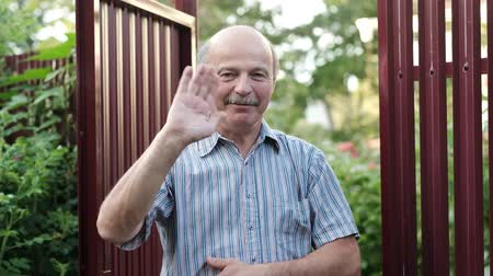 saying : Friendly caucasian old man waving hi or farewell, isolated outdoors background with green trees and fence. Homeowmer saying goodbye to his guest