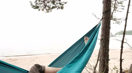 hamak : Young caucasian male resting lying on blue hammock outdoors near lake. Have calm vacation in Russia