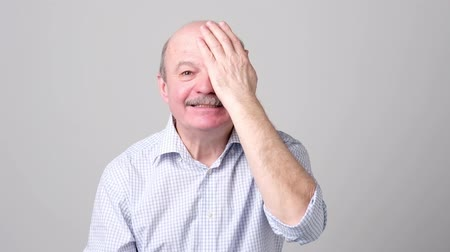blindness : man covering one eye during vision examination trying to see letters.