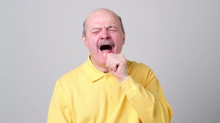 bezsennosć : sleepy man in yellow shirt yawning, morning and wake up