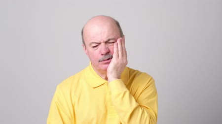 grimacing : Senior man suffering with terrible toothache