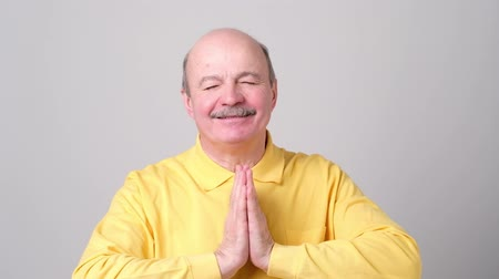 угождать : mature man in yellow shirt showing clasped hands,asking for help from God.