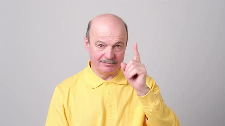 Strict senior man showing index fingers up, giving advice