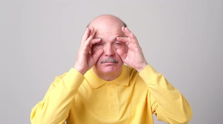 Sleepy senior man trying to open his eyes with fingers. Стоковые видеозаписи