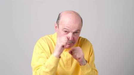 выражающий : Mature bald man raising fists as defending or fighting, expressing confidence