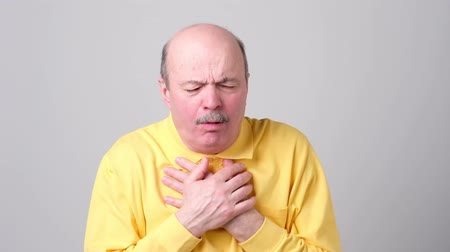 Mature hispanic man in yellow t-shirt man coughing being ill.