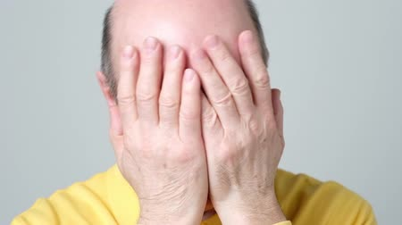 Close up of a stressed elder man closing his face with hands. Стоковые видеозаписи