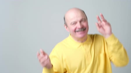 výstřední : Expressive old man in yellow shirt dancing on birthday party.