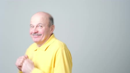 Expressive old man in yellow shirt dancing on birthday party.