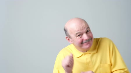 különc : Expressive old man in yellow shirt dancing on birthday party.